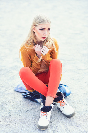 Young blond model with straight hair in bright outfit sitting on street with legs crossed and holding her arms crossed at her chest