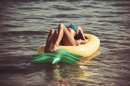 Sexy woman on Caribbean sea in Bahamas. Pineapple inflatable mattress, activity and joy. Maldives or Miami beach water. Girl sunbathing on beach with air mattress. Summer vacation and travel to ocean Banco de Imagens
