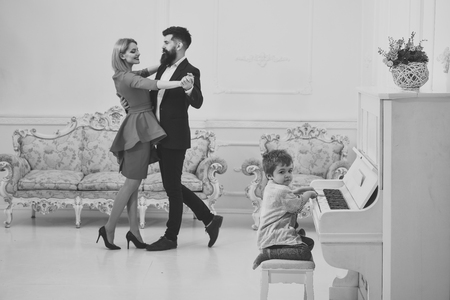 Rich parents enjoy parenthood. Boy adorable try to play piano musical instrument, while parents dancing. Child sit next to piano, play music, white interior background. Musician education concept.