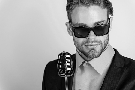 man in glasses sing in microphone. Stock Photo