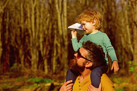 Flying is the perfect vocation for a man who wants to feel like a boy. Little son dream of flying on fathers shoulder. Child boy and father launch paper plane in park Stock fotó - 116493261