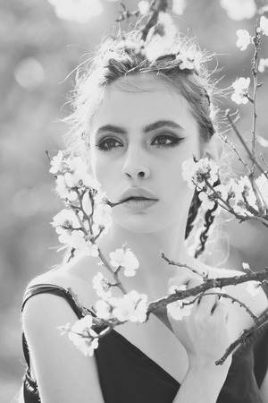 pretty girl with fashionable makeup among spring blooming cherry flowers Stockfoto