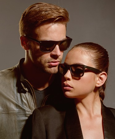 The strongest relationship. Couple in love. Couple of man and woman wear fashion glasses. Love relations. Friendship day. Fashion models in trendy sun glasses. Friendship relations. Casually handsome Archivio Fotografico - 116493437