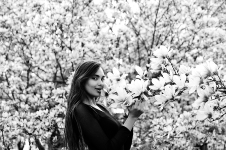 woman with long, brunette hair posing at magnolia tree