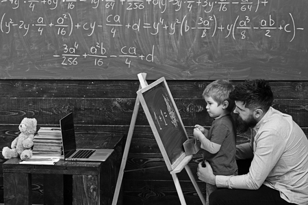 Pupil with teacher at school. Side view father and son learn arithmetic. Daddy explaining equation to cute kid