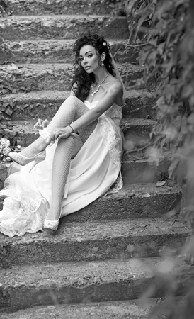 Girl with bridal makeup and hairstyle. Woman wear lace garter on leg. Sexy woman in stockings lingerie on wedding day. Bride in white dress sit on steps outdoor. Wedding fashion and accessory Stockfoto