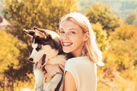 Canine companion. Happy dog owner play with family pet outdoor. Sexy woman with dog pet on summer day. Happy girl hold pedigree dog. This girl loves her siberian husky