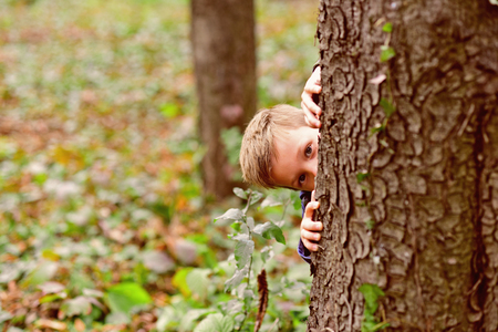 Let your kid play. Little boy play hide and seek game. Little boy play nature. Every day get outside and play Фото со стока