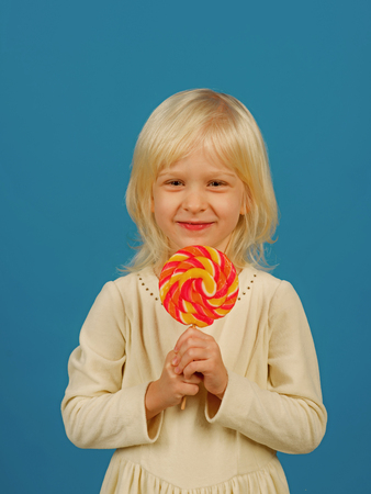 Bold hard candy creation. Small child with sweet lollipop. Small girl hold lollipop on stick. Happy candy girl. Happy childhood food Stock Photo