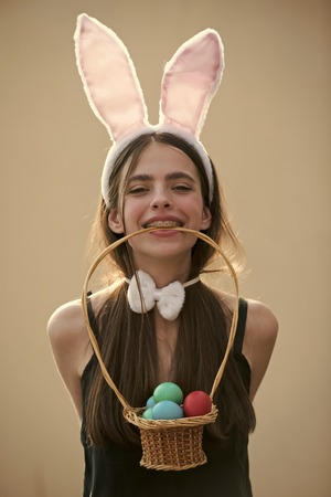Easter woman with bunny ears and bow on beige background