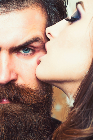 Woman kiss bearded man with love. Woman with makeup skin and hipster with long beard Stok Fotoğraf