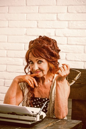 Being experienced. Female reporter or journalist writing on typewriter. Senior woman type on retro typewriter. Old woman work in writer office. Journalist work in vintage office. Aged writer at desk Фото со стока
