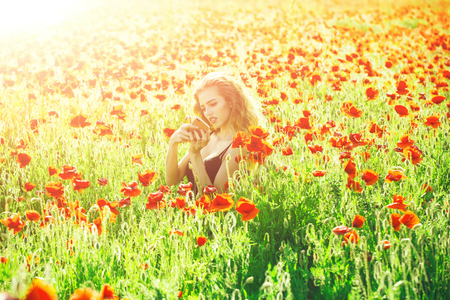 young girl in a poppy field with mobile phone Stock Photo