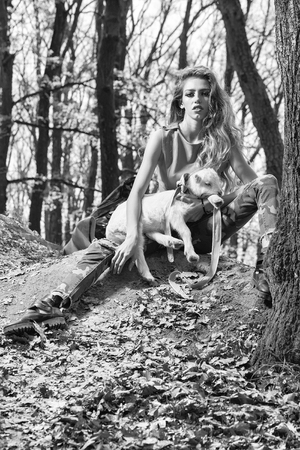 Stylish girl with goat in forest