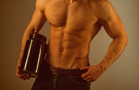 Energy diet. Man with six pack abs. Strong man hold vitamin bottles. Vitamin nutrition. Stimulating muscle growth with anabolic steroids. Anabolic hormone increases muscle strength. Healthy diet Stock Photo