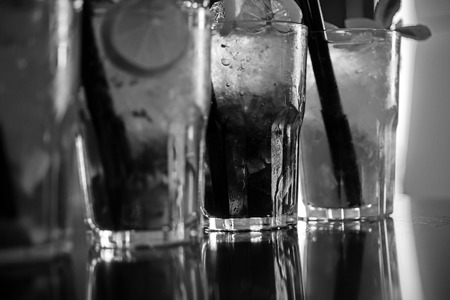 Enjoy a drink. Iced drinks in cocktail glasses in bar. Alcoholic mixed drinks with ice. Juicy beverages with alcohol on counter. Alcohol addiction. Cocktails served in glasses with drinking straws