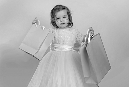 happy childhood of little girl. Kid shopping. shopping bags. Christmas gift. Thanks for your purchase. big sale in shopping mall. Happy birthday. New year party. small girl child with present package
