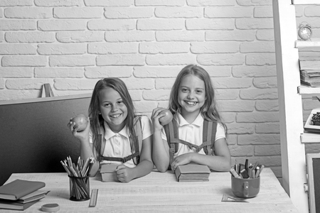 Little girls eat apple at lunch break. Friendship of small sisters in classroom at knowledge day. School time of girls. Happy school kids at lesson in september 1. Back to school and home schooling