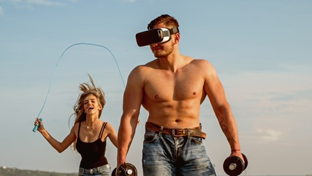 Workout on blue sky. Workout with VR and gym equipment. Man and woman have workout on fresh air. Workout and training. Technology you can trust