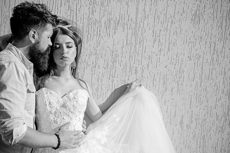 They love fashion and glamour. Romantic couple in love. Sensual bride in white wedding dress. Bearded groom in casual wear. Man and woman of fashion. Couple of lovers with fashion style