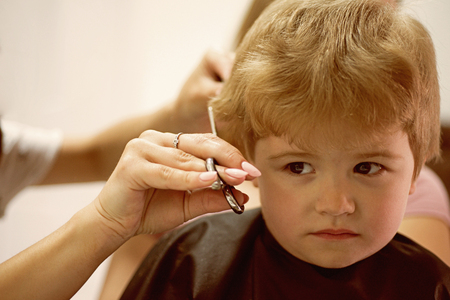 Haircut that your kid will love. Cute boys hairstyle. Kids hair salon. Little child given haircut. Small child in hairdressing salon. Little boy with blond hair at hairdresser. Kids barber at work