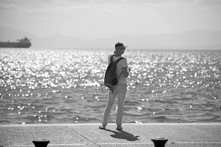 man traveler with backpack looking far away at sea water. travel and wanderlust concept. summer vacation and adventures. young man is going to marine trip. futute life concept