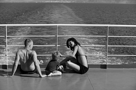 Mother and father with son in sea on yacht. Family travel with kid on mothers or fathers day. Love and trust as family values. Child with father and mother. Summer vacation of happy family.