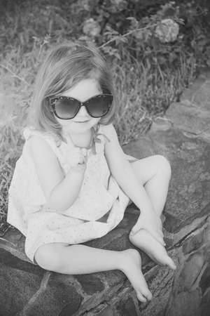 Baby girl smiling in sunglasses with raised finger Stockfoto
