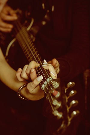 Feeling the music. Male and female hands play the electric guitar. Couple of guitar players. Couple of musicians enjoy playing music. Couple in love play duets. Instrumental music live Reklamní fotografie