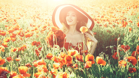 flower bouquet at smiling girl in retro hat, poppy field Stock Photo