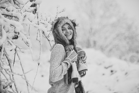 Happy woman smile with figure skates at trees in snow
