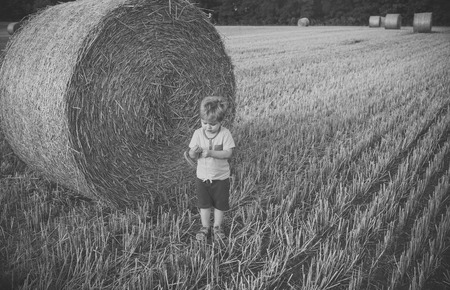 Child and bales of hay on field