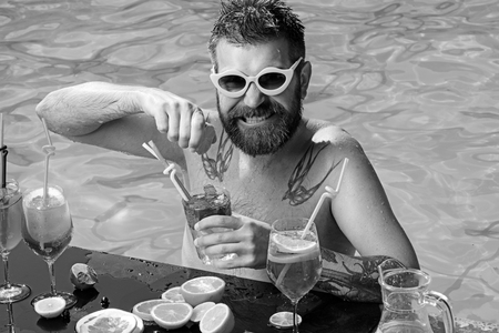 Man swimming and drink alcohol. man with cocktails in swimming pool bar.