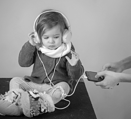 having fun. little girl child smiling. winter kid fashion. small happy girl. childhood and happiness. Looking trendy. Confident in her choice. kid listen music with headset and mp3 on phone Banque d'images - 116210791