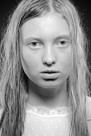 Sensual blond young woman with wet hair look at camera