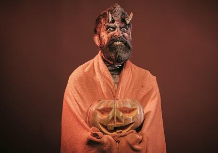 Halloween demon scary in blanket with jack o lantern Stock Photo