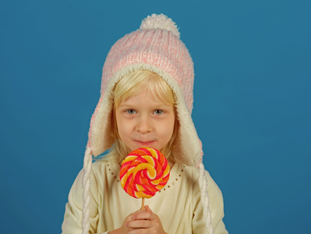 Snack on when you please. Little child with sweet lollipop. Little girl hold lollipop on stick. Happy candy girl. Happy childhood food