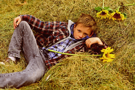 Totally carefree. Small boy relax in hayloft. Small boy in farm barn. Hayloft in countryside. Just relaxing