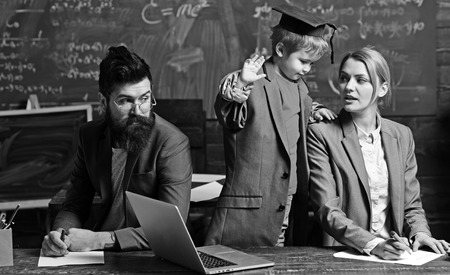 Child teach woman and man in school. Child in big suit coat and graduation cap together with family at desk, examination