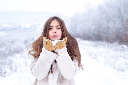 Love winter. Happy cool girl blowing red lips makes air kiss wearing a white sweater over snowy background. Lovely girls in winter vacation. Winter woman blowing pink lips sends air kiss.