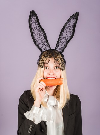 Surprised bunny woman wearing bunny ears and eat carrot. Happy easter and funny easter day. Smile easter.