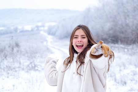 Snowball game in happy winter. Playing with snow and having fun in winter park. Activity smiling girl in winter travel. Having fun in winter holiday. Enjoying the weather and snowball game.