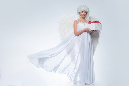 Girl with angel wings and a white dress. Angel girl. Cupid woman. Stock fotó