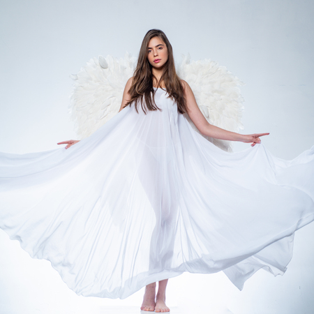 Girl with angel wings and a white dress. Cupid woman.