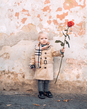 Little valentine boy. Cute boy hiding red rose. St Valentines Day concept. Stock Photo