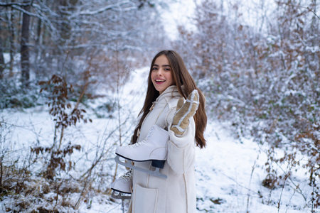 Laughing Girl Outdoors. Model wearing stylish sweater and gloves. Portrait of a young woman in snow trying to warm herself. Winter woman.
