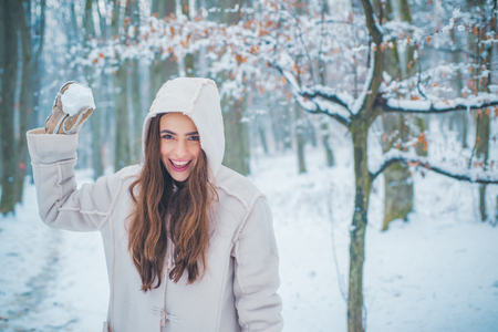 Winter portrait of young beautiful brunette woman in snow Garden. People in snow. Woman winter portrait. Banco de Imagens