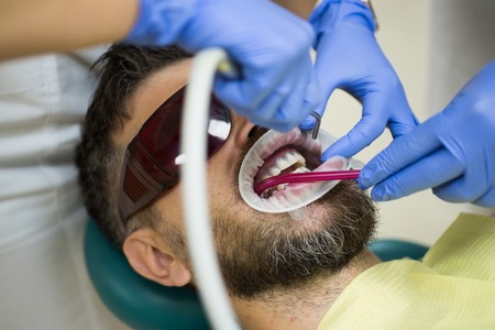 Handsome man at dentists office. Female dentist checking patient teeth with mirror in modern dental clinic. Examine of young man by dentist on light blurred background. Stock Photo