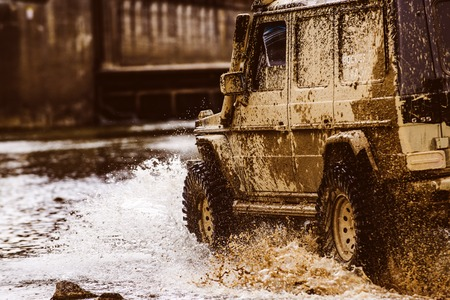 Mud and water splash in off the road racing. Bottom view to big offroad car wheel on country road and mountains backdrop. Off-road vehicle goes on the mountain. Stock Photo