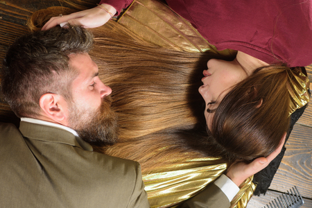 Woman with beautiful long hair with man with long beard on wooden background. Long healthy hair. Fashion haircut.